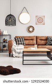 Brown leather couch with blanket and patterned cushions in real photo of bright living room interior with coffee table with lemon water and book and mirror, clock and poster on the wall