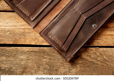 Brown leather empty opened purse on wooden background