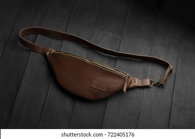 brown leather fanny pack on black background