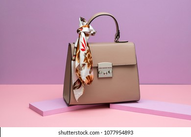 Brown leather female bag with a colorful silk scarf on the small pink boards on the peach surface on the violet background in the studio. Closeup. Horizontal.