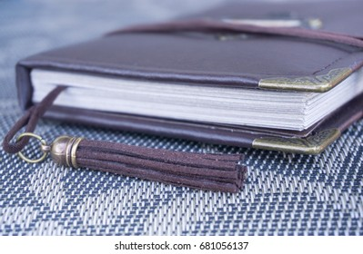 Brown leather handmade scrapbooking notebook for travellers scraps and memories, made as a gift, with tassel, corners and lace as decoration