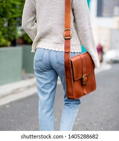 A brown leather handmade shoulder bag carried by a woman in a winter top and light blue jeans
