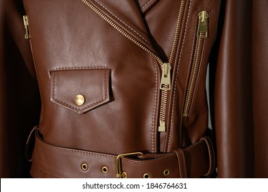 Brown leather jacket with metal zippers on it. Stitched leather. Closeup. Horizontal fashion background.