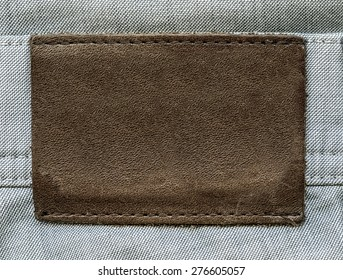 brown leather label on gray jeans background