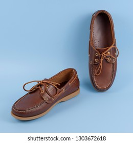 Brown leather men loafers shoes isolated on a blue background. Fashion advertising shoes photos.