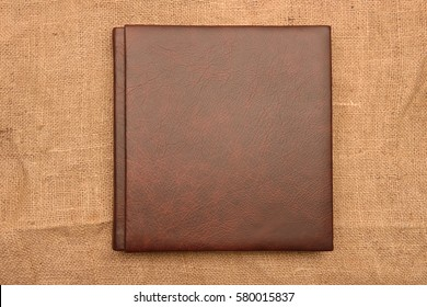 brown leather photo album cover on jute background. Keeping memories alive throughout the years concept