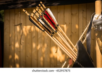 A brown leather quiver full with hand crafted arrows in medieval style each arrow with different color on the feather
