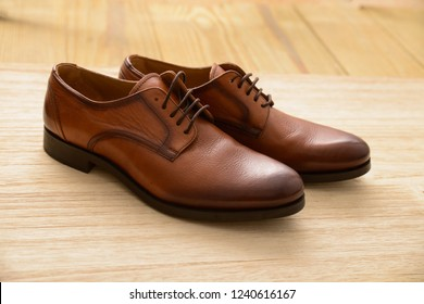 Brown leather shoes isolated on a wooden background