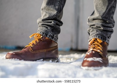 Brown leather shoes in the snow. Legs in the warmth concept