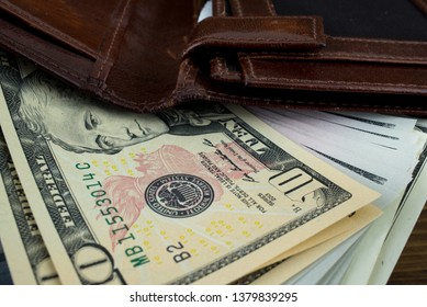 Brown leather wallet with money us dollars inside it. Macro photo.