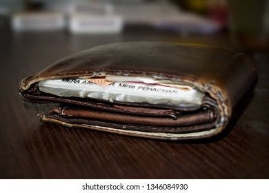 Brown leather wallet. On top of a table with aadhar card in it.