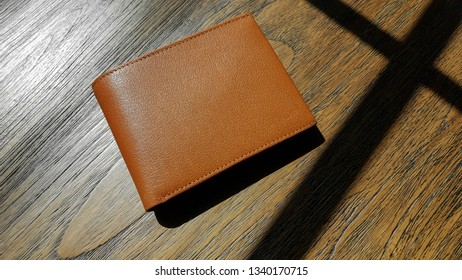 Brown leather wallet on wood background.