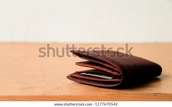 Brown leather wallet put on wooden table top