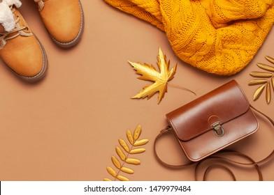 Brauner Lederbeutel, orangefarbener Pullover, warme Stiefel, goldenes Herbstblatt auf braunem Hintergrund, Draufsicht flach. Modische Frauenzubehör. Modekonzept Herbst. Stylische Damenkleidung