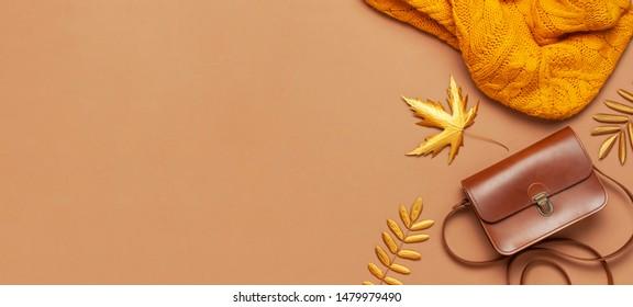 Brauner Lederbeutel, orangefarbener Pullover, goldenes Herbstblatt auf braunem Hintergrund, Draufsicht, Kopienraum. Modische Frauenzubehör. Modekonzept Herbst. Stylische Damenkleidung