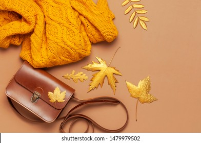 Brown leather women bag, orange knitted sweater, golden autumn leaf on brown background top view flat lay copy space. Fashionable women's accessories. Autumn Fashion Concept. Stylish Lady Clothes