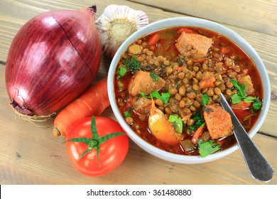 Brown lentil Soup and ingredients carrots, bulbs red onion and Garlic, Tomato, smocked sausage, seasonings parsley, dill in gray porcelain bowl over gray wooden table