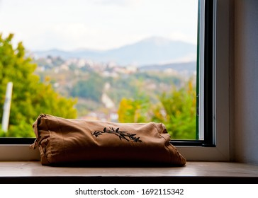 Brown linen cushion with bamboo filling and embroidered decorations in black on the window with trees in the background. Ovada Italy october 10th 2017