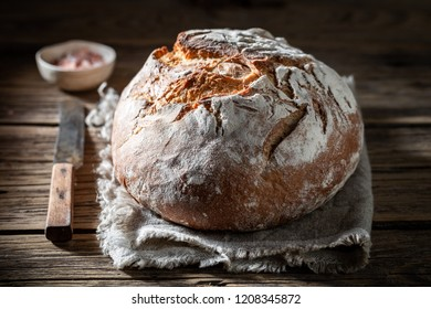 Brown loaf of bread with salt on wooden table