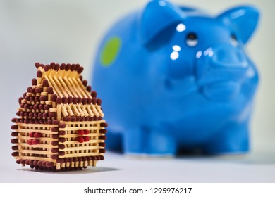 Brown matchhouse in foreground with blue, slightly blurred piggy bank in the background