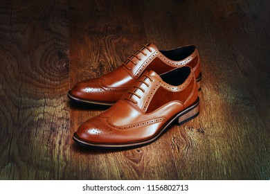 Brown men's shoes on wood background