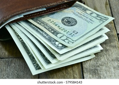 brown men's wallet and dollars on wooden background