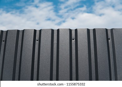 Brown metal plate against blue cloudy sky. Siding. Seamless surface of galvanized steel. Industrial building wall made of corrugated metal sheet, flat background photo texture.
