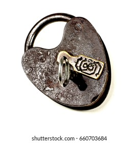 Brown metal rusted antique padlock locked with key in the keyhole