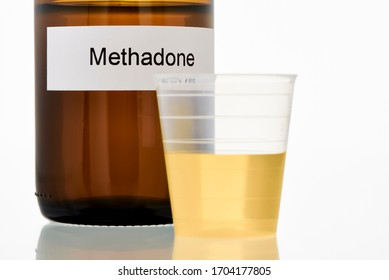 A brown methadone bottle and in front of it a cup with a dose of methadone to take