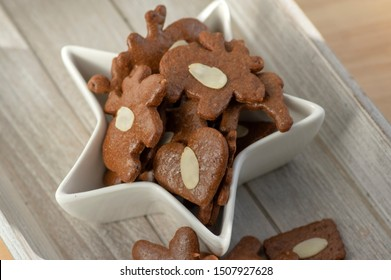 Brown moravian dark gingerbreads with sliced almonds, christmas cookies in white star shapped bowl on light wooden table background