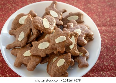 Brown moravian dark gingerbreads with sliced almonds, christmas cookies on white plate on glittering gold red tablecloth