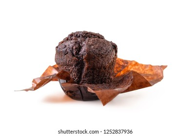 Brown muffin with chocolate in dark brown parchment paper isolated on white background