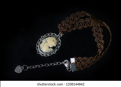 Brown necklace with girl cameo on a dark background close up