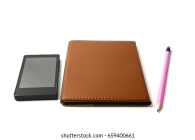 Brown notebook  With a pencil and Smartphone  placed beside On a white background.