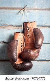 Brown old boxing gloves with a lace over old blue wall with peeling paint