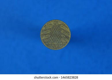 brown old german coin with coat of arms on a blue background