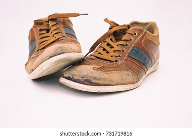brown old sneakers with brown shoelaces.