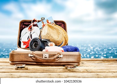 Brown old suitcase on wooden desk space and landscape of sea with sky. Free space fo ryour decoration.