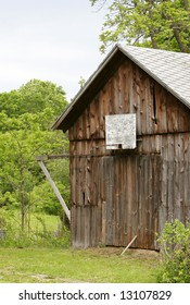 brown old weathered barn with a broken basketball hoop on the side