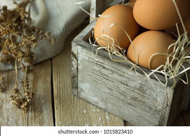 Brown Organic Eggs on Straw in Vintage Wooden Box on Plank Kitchen Table Linen Napkin Dry Flowers. Easter Composition in Rustic Authentic Style. Copy Space