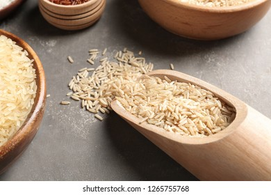 Brown and other types of rice on grey table, closeup view