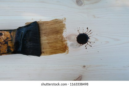 A brown paint blob with brush and streaks of wood stain on untreated wood