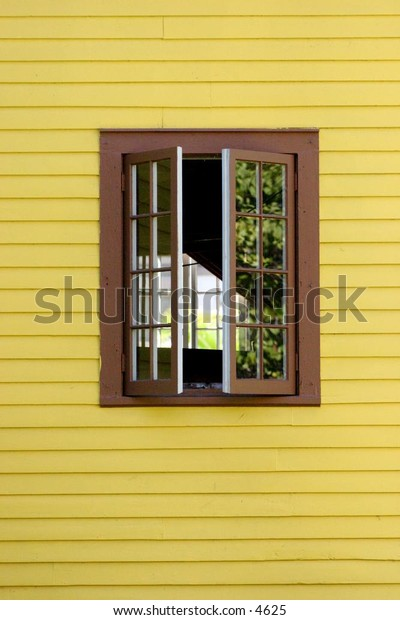 brown paned windows open from yellow building