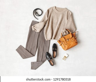 Brown pants in check, beige knitted oversize sweater, bag, belt, perfume, black loafers or flat shoes on grey background. Overhead view of women's casual day outfit. Flat lay, top view. Women clothes.
