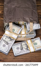 Brown paper bag containing that moolah. Bag full of money - vintage photography of brown paper bag with stacks of hundred dollar bills on wooden background