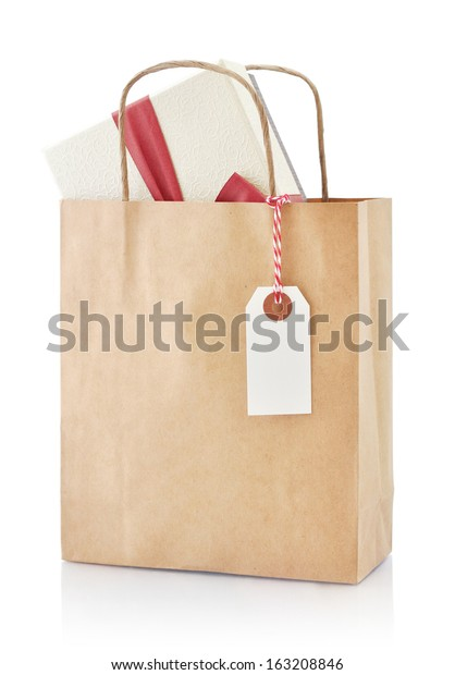Brown paper bag with gift and paper tag isolated on a white background