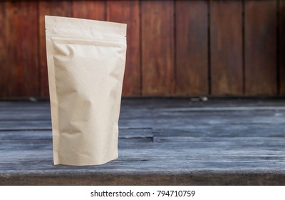 Brown paper bag with space on wood background, tea bag packaging