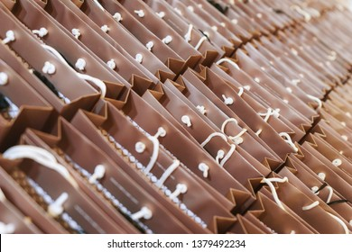 Brown paper bags with handles filled with gifts for holiday guests and events. A lot of bright paper bags with souvenirs. Abstract background and soft focus.