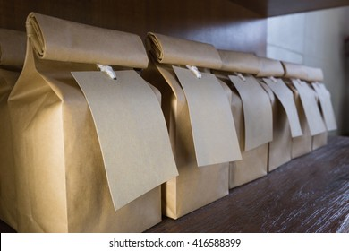 Brown paper bags with brown paper labels hanging from white strings, on wooden shelves, selective focus on the closest bag's label