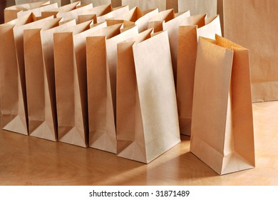Brown paper bags on wooden table in morning sunlight.